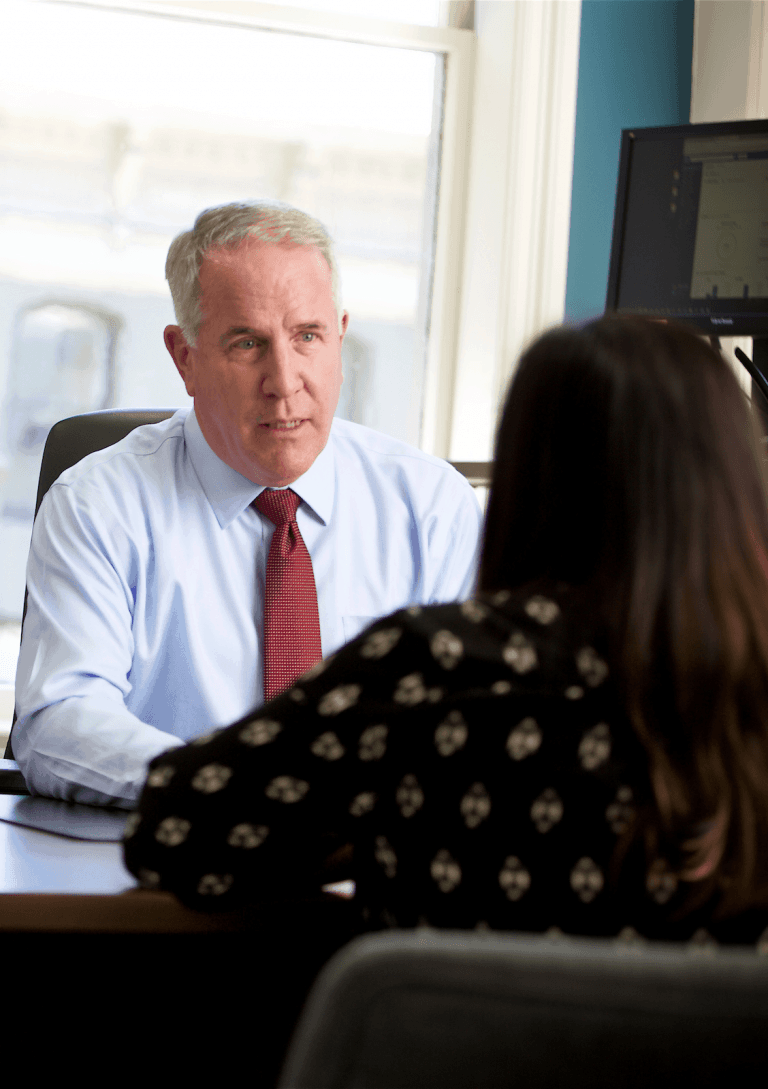 Gregory Zeuthen at desk speaking with female client